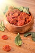 stock photo of apricot  - Dried apricots in a wooden bowl - JPG