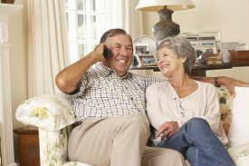 stock photo of retirement  - Retired Senior Couple Sitting On Sofa Talking On Phone At Home Together - JPG