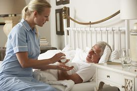 picture of nursing  - Nurse Giving Senior Male Medication In Bed At Home - JPG