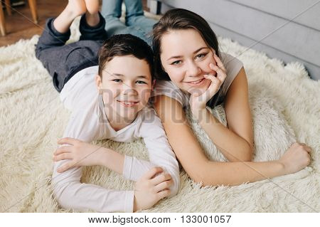 Brother and sister pose smiling while lying on the floor at home