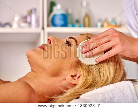 Portrait of woman middle-aged take face cleaning in spa salon. Spa procedure for middle-aged woman.