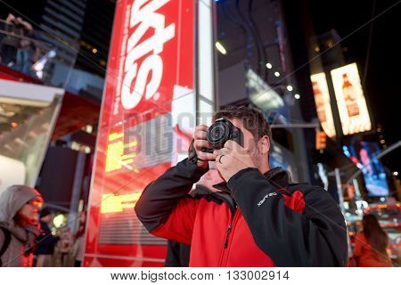 NEW YORK - CIRCA MARCH, 2016: man taking photos in New York at nighttime. The City of New York, often called New York City or simply New York, is the most populous city in the United States