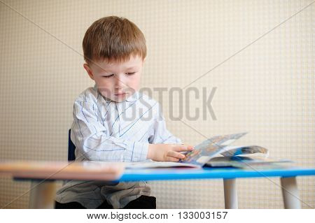little boy at the desk reading a book.