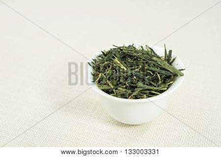 Tea (Sencha) in white bowl on white background.