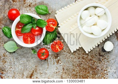 Ingredients for making Italian lasagna caprese - fresh basil cherry tomatoes baby mozzarella cheese fresh pasta on old metal background blank space for text recipe top view