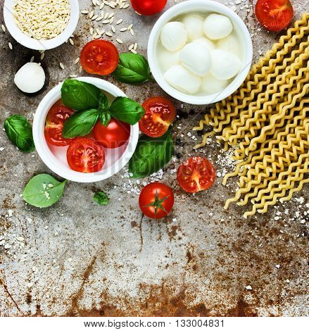 Ingredients for cooking pasta caprese - fresh basil cherry tomatoes baby mozzarella cheese fresh pasta fusilli lunghi and parmesan on old metal background blank space for text recipe top view
