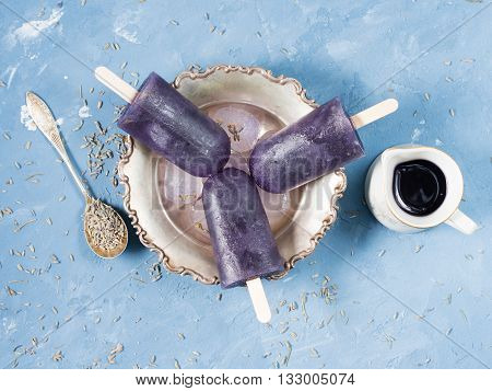 Lavender popsicles made of frozen orange and lemon juice with lavender syrup in a silver bowl on blue background with culinary lavanda flowers and syrup