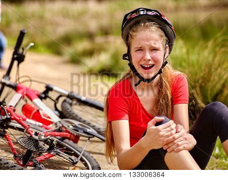 Bikes cycling girl. Girl rides bicycle. Girl girl fell off bicycle. Bicycle girl keeps self for bruised knee.