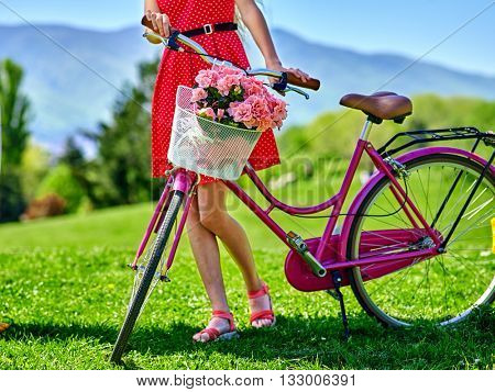 Body part bicycle girl wearing red polka dots dress rides bicycle into park.
