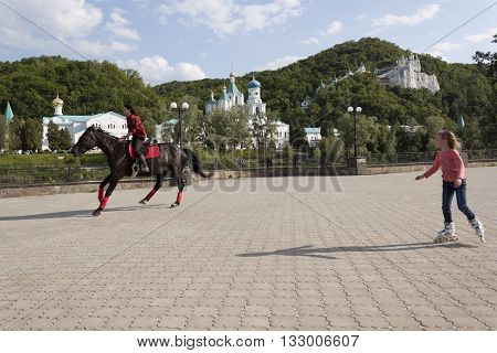 SVIATOHIRSK UKRAINE - MAY 22 2016: Unidentified girls on a horse and roller skates. On the waterfront Svyatohirsk everyone will find something to do on horseback or on roller skates