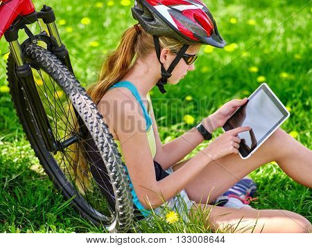 Bikes cycling girl. Girl rides bicycle. Girl in cycling sitting on green grass near bicycle and watch pc tablet. Cycling is good for health. Cyclist looking for road.