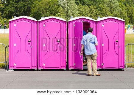 four portable, pink toilets on a street