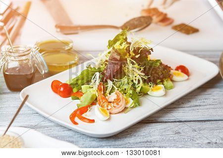 White plate with salad. Salad with shrimp and eggs. Frisee and cherry tomatoes. Natural food at local restaurant.
