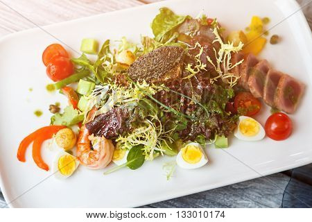 Plate with pile of salad. Salad with tomatoes and shrimp. Frisee lettuce and cherry tomatoes. Boiled egg and fried tuna.