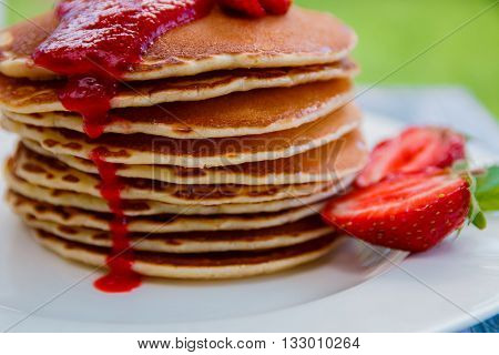 Pancakes with fresh strawberry and jem on white plate on white wooden background in garden or on nature background. Stack of pancakes on the table. Closeup.