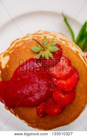 Top view of pancakes with fresh strawberry and jem on white plate. Stack of pancakes on the table.
