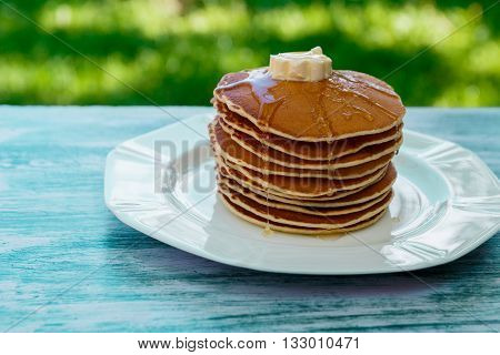 Pancakes with butter and honey on white plate on blue wooden background in garden or on nature background. Stack of wheat golden pancakes or pancake cake closeup.