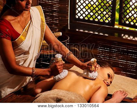 Woman having Ayurveda massage with herbal ball. Alternative massage.