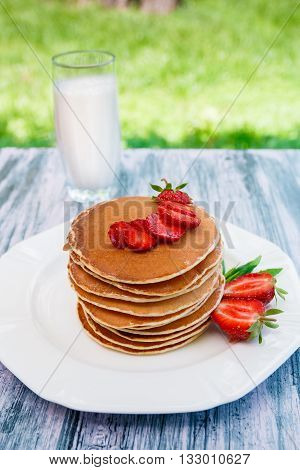 Pancakes with fresh strawberry and mint near glass with milk on white plate on pink wooden background in garden or on nature background. Stack of pancakes on the table.