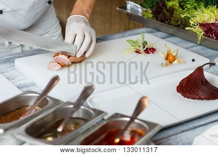 Knife cuts cooked meat. White plate with cooked pear. Chef cuts duck steak. Sweet fruit and fried meat.