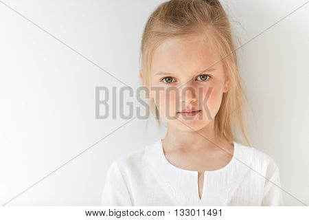 Close Up Portrait Of Little White-skinned Girl Looks Straight Forward And Closely Watching You. Blon