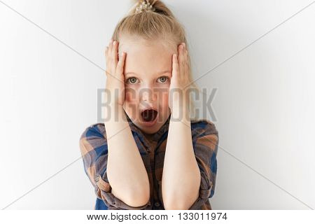 Blond Scared Child Looking At Camera Holding Head With Her Hands. She Is Gaping, Her Eyes Are Wide-o