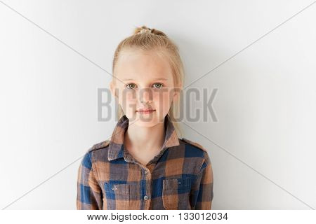 Cute Blond Girl With Posing On White Background. Portrait Of Relaxed Kid With Nice Kind Look. Calm A