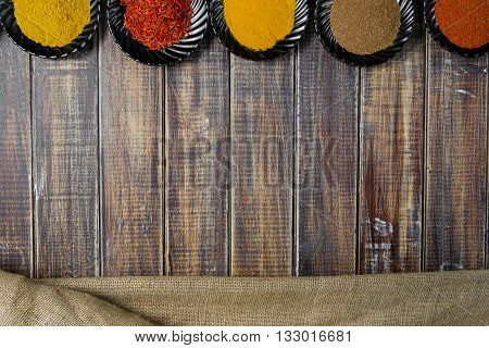 Spices in black ceramic plates on wooden background. Various spices selection. Six plates with different colorful spices near sackcloth top view. Frame. with copy space
