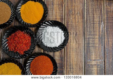 Spices in black ceramic plates on wooden background. Various spices selection. Six plates with different colorful spices top view. Frame. with copy space