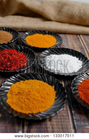 Spices in black ceramic plates on wooden background. Various spices selection. Six plates with different colorful spices