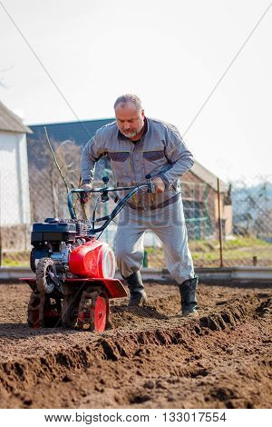Man working in the garden with Garden Tiller. Garden tiller to work. Man with tractor cultivating field at spring