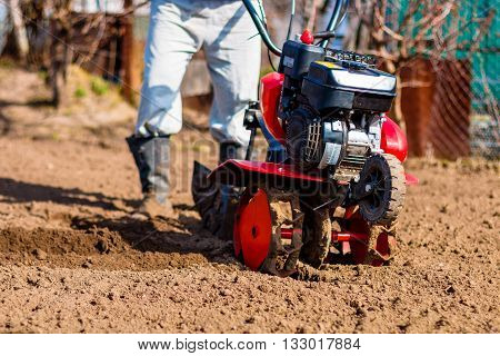 Man working in the garden with Garden Tiller. Garden tiller to work closeup. Man with tractor cultivating field at spring