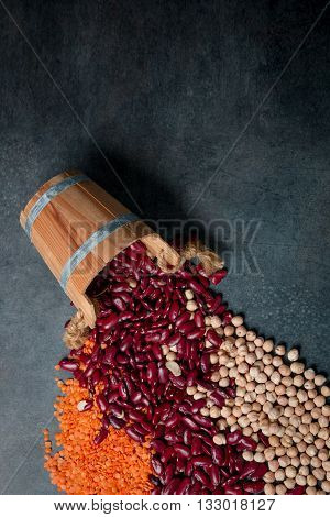 Group of beans lentils and chick-pea in wooden cup on black background. beans assortment. Beans variety