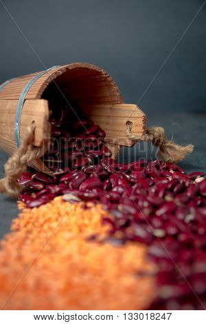 Group of beans and lentils wooden cup on black background. beans assortment. Beans variety closeup