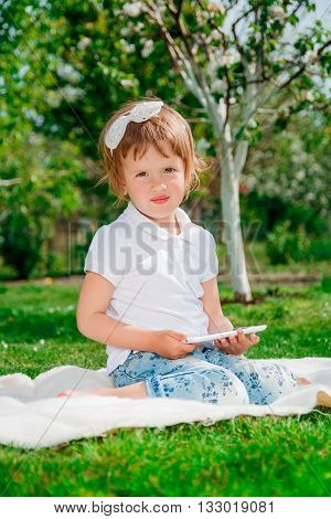 Little baby girl dressed in white polo and jeans barefoot sitting with tablet on white fur blanket in park with blossoming trees in the background. Girl Using a Tablet. looking at the camera