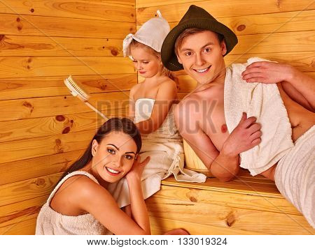 Happy family with child in hat relaxing at sauna. Family sauna.
