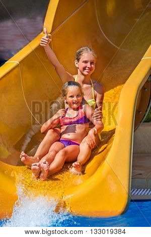 Two children together on water slide at aquapark show thumb up. Summer swimming holiday. There are two water slides in swimming aqua park. Outdoor.
