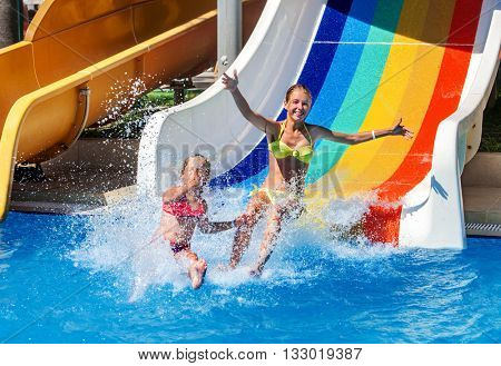Two children on water slide at aquapark show thumb up. Summer swimming holiday. There are two water slides in aqua park. Swimming outdoor.