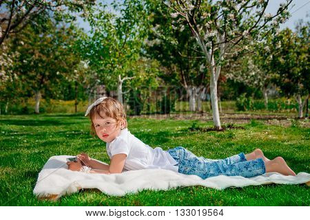 baby girl dressed in white polo and jeans barefoot lying with tablet on the fur blanket in the park with blossoming trees in the background. kid's hold tablet smartphone phone for playing and education.