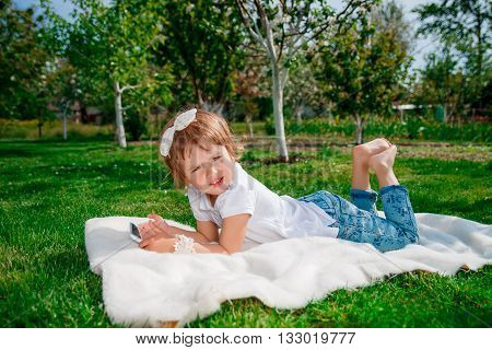 baby girl dressed in white polo and jeans barefoot lying with tablet on the fur blanket in the park with blossoming trees in the background. Little girl Using a Tablet.
