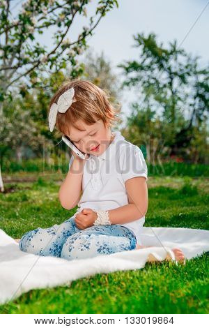 cute little girl talking on the phone. Little baby girl dressed in white polo and jeans barefoot sitting with mobile phone sitting on the white cover in the park.