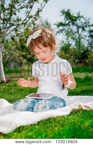 baby girl dressed in white polo and jeans barefoot sitting with tablet on the white fur cover in the park with blossoming trees in the background. Little girl play a game on tablet.