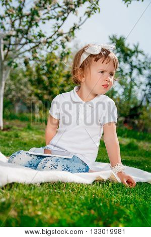 Little baby girl dressed in white polo and jeans barefoot sitting with tablet on white fur cover in park with blossoming trees in background. Girl Using a Tablet.