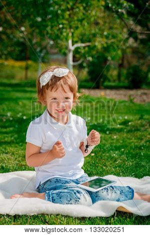 HAppy Little baby girl dressed in white polo and jeans barefoot sitting with tablet on the white fur cover in the park. Girl Using a Tablet.
