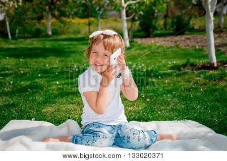 cute little girl talking on the phone. Little baby girl dressed in white polo and jeans barefooted with mobile phone sitting on the white fur cover in the park