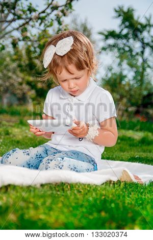 baby girl dressed in white polo and jeans barefoot sitting with tablet on the white fur cover in the park. Little girl studies with the tablet