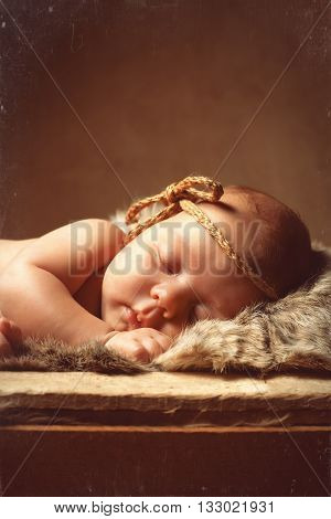 Newborn sleeping baby in wooden box with fur. Cute newborn baby girl.