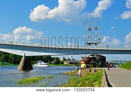 VELIKY NOVGOROD RUSSIA -JUNE 32016. Promenade along the Volkhov river with pedestrian bridge and Frigate Flagship reastaurant in summer day