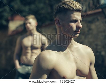 Young man sexy muscular bodybuilder macho with bare torso stylish haircut while twin brother poses outdoor on blurred background