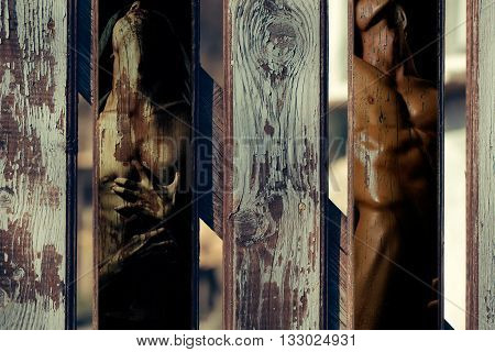 Wodden fence with double exposure of handsome young man with sexy bare torso combined with timber texture